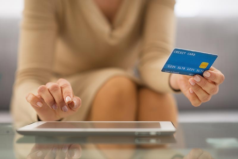 Woman with credit card using tablet